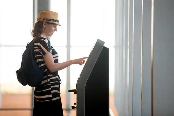 Woman checking in at the hotel self-service kiosk Clock Kiosk