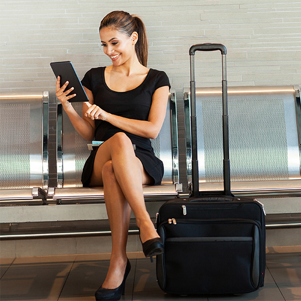 Woman with tablet using the hotel online check-in of Clock PMS Suite